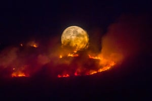 A full moon rises behind burning moorland as a large wildfire sweeps across the moors between Dovestones and Buckton Vale in Stalybridge, Greater Manchester 26 June 2018