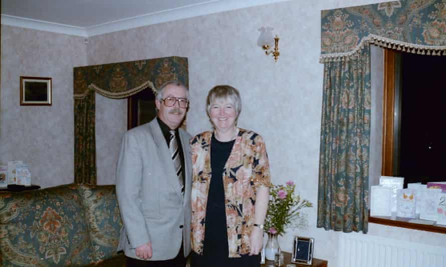 Judith and Peter, dressed in smart party clothes, in their living room with chintz curtains