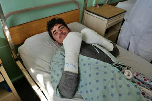 Ehsanullah, 19, lies in a hospital bed with his hands wrapped in bandages after a bomb went off as searched for belongings amid the rubble of his home in Kandahar.