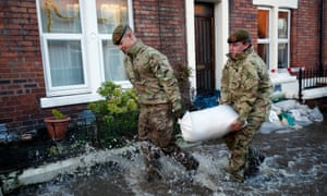 Members of the armed forces help distribute sandbags to residents following flooding in Carlisle.