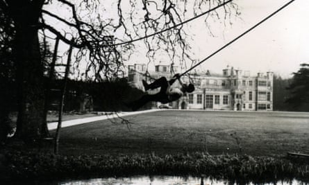 man swings himself on a rope over a lake in the grounds of a big house