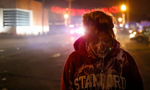 A protester stands in the street after being treated for tear gas exposure in Ferguson