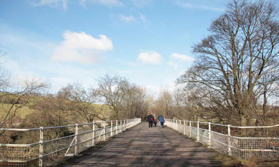 Walkers crossing the old railway bridge over the Swale by Easby Abbey, outside Richmond, North Yorkshire.