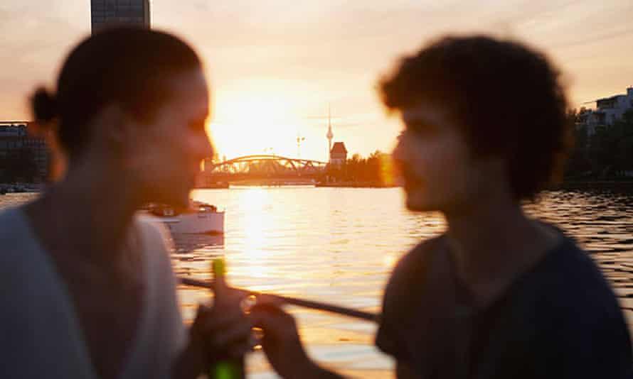 Germany, Berlin, Young couple on boat, holding bottles, side view, portraitC5WFGJ Germany, Berlin, Young couple on boat, holding bottles, side view, portrait