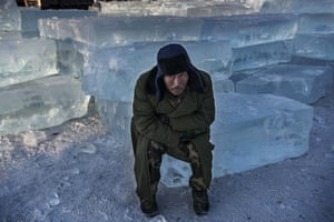 A worker sits on ice as he takes a break
