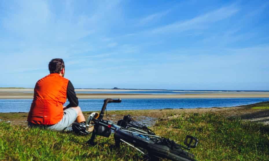 man and bike looking across water