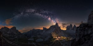 Guardian of Tre CimeCarlos F. Turienzo (Spain). This panoramic image, composed out of eight photos, depicts the Milky Way emerging over the rocky Dolomites in Tre Cime on the left, and on the right the lights from a house illuminating the beautiful terrain.