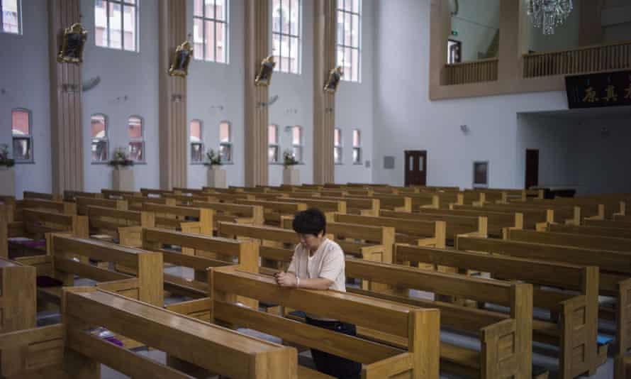 A woman prays at a Catholic church in Tianjin, China