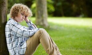 Worried-looking boy leaning against tree