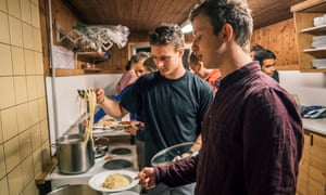 Group of men cooking in communal kitchen