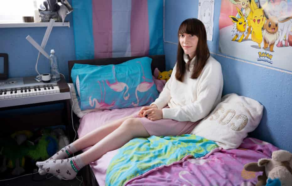 Hannah in her room, in front of a Pokémon poster
