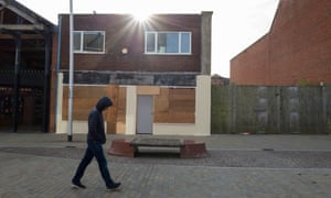 A man walks past shuttered buildings in Barrow-in-Furness