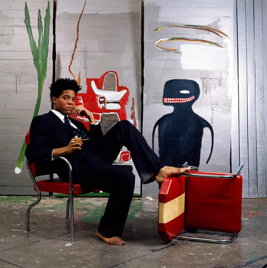 Jean-Michel Basquiat wearing Giorgio Armani, seating in front of his work.