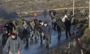 Settlers run from Israeli police outside the Amona outpost in the West Bank on Wednesday morning.