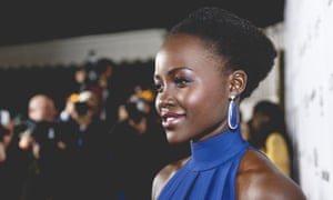 Lupita Nyong'o posing for a crowd of photographers at an event