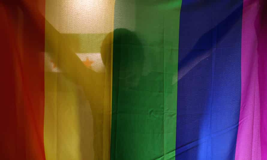 A man behind a rainbow flag