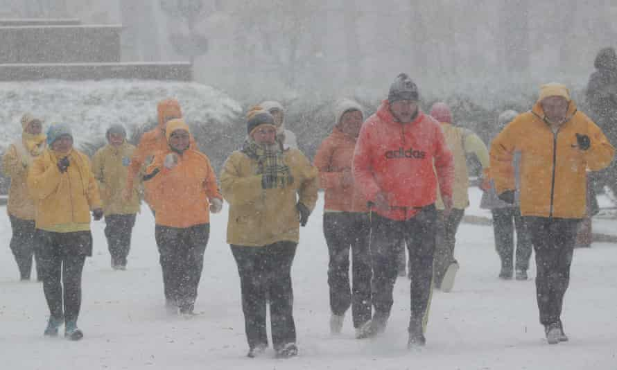 No pay-in, no gain: people exercise at a park amid a snow flurry in central Kiev.