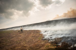 Farmer Stephen Frost attempts to beat back a wildfire spreading across the moorland towards his farm above the village of Rhewl in North Wales.