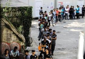 Migrants wait in a queue to receive food and beverage near Croatia's border in Bihać, Bosnia-Herzegovina