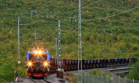 View of an Electrical Ore Line Train in speed comes in. Autumn, and lights on.
