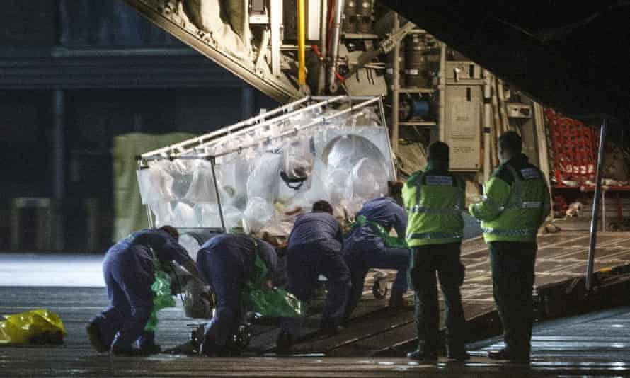 Medical personnel wheel a quarantine tent trolley containing Scottish healthcare worker Pauline Cafferkey after returning to Scotland from Sierra Leone, into a plane at Glasgow International Airport.