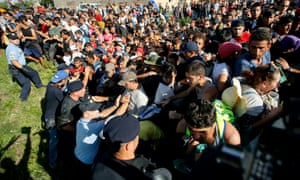 Migrants push policemen during a stampede to board buses in Tovarnik, Croatia