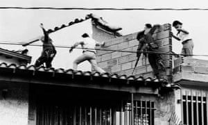 Police and military forces storm the rooftop where drug lord Pablo Escobar was shot dead in 1993.