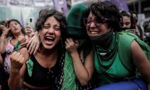 Two women wearing green look happy