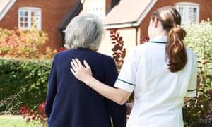 A carer helping an elderly woman to walk