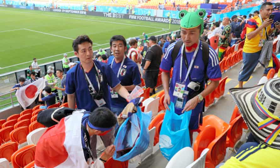 Japanese supporters clean the stand after their match with Colombia.