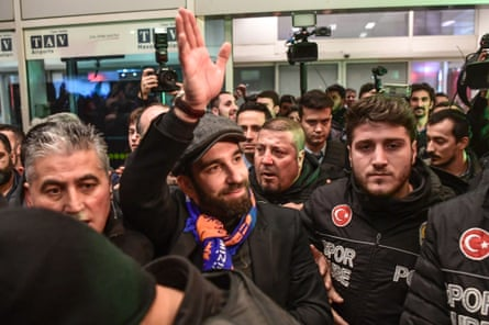 Arda Turan waves to supporters while being escorted by police officers as he arrives in Istanbul.
