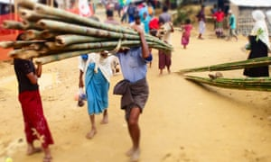Children carrying bamboo in the camp.