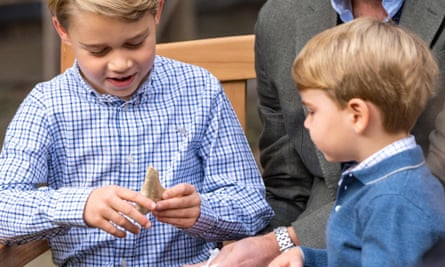 Prince Louis (right) watching as Prince George (left) holds the giant shark tooth given to him by Sir David Attenborough in the gardens of Kensington Palace.