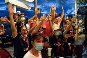 Paris Saint-Germain supporters react at a cafe terrace in Paris.