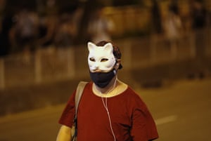 A defiant masked protester walks the streets of Hong Kong.