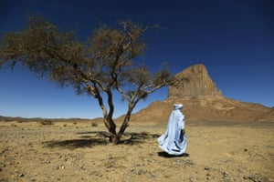 A Tuareg poet in a blue robe walks on the sand of the Tagmart plateau