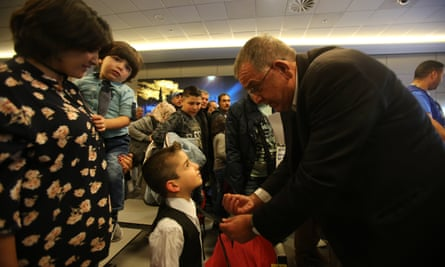 Ioannis Mouzalas talks to a refugee child at Athens international airport last month