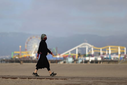 A woman walks the beach in Santa Monica. Southern California is seeing a particularly troubling rise in cases.