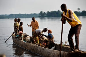 A man paddles a pirogue carrying people to a health centre near Isangi