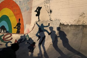 Young men cast shadows as they practise their rollerblading and skating skills.