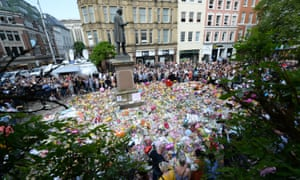 Crowds look at the floral tributes after a minute's silence in St Ann's Square, Manchester, to remember the victims of the attack.