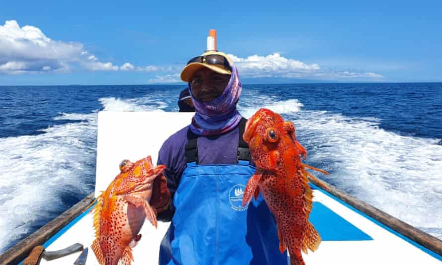 Walter Borbor, a small-scale fisherman, holds his catch of scorpion fish, or brujo. He must make longer fishing trips for smaller catches as he competes with huge facotry ships near the Galapagos marine reserve.