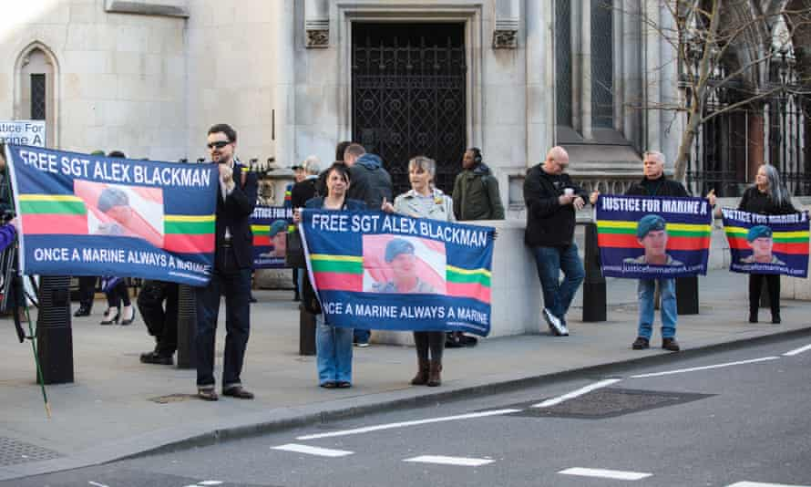 Supporters of Blackman hold up a banners outside the royal courts of justice in London on Wednesday.