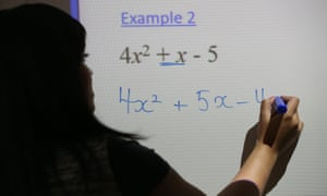 A teacher writes an equation on a whiteboard during a maths lesson