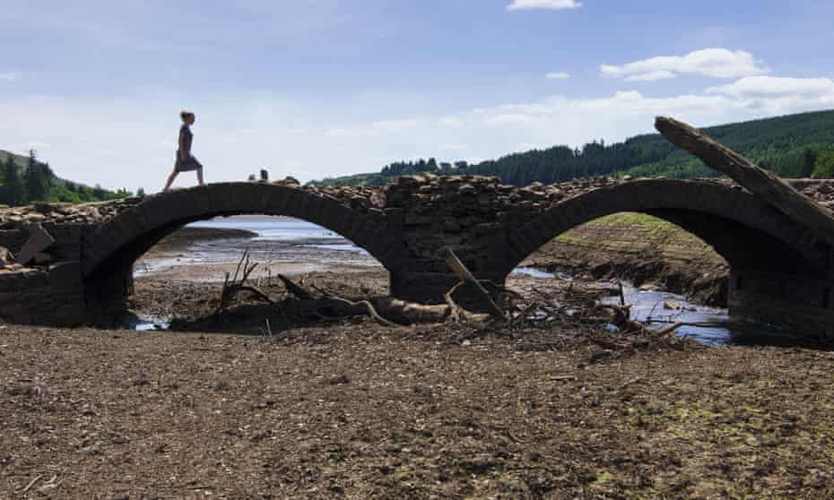 A woman crosses a bridge at the Llwyn-on reservoir, near Merthyr Tydfil, Wales, which has vastly reduced water levels as a result of the heatwave