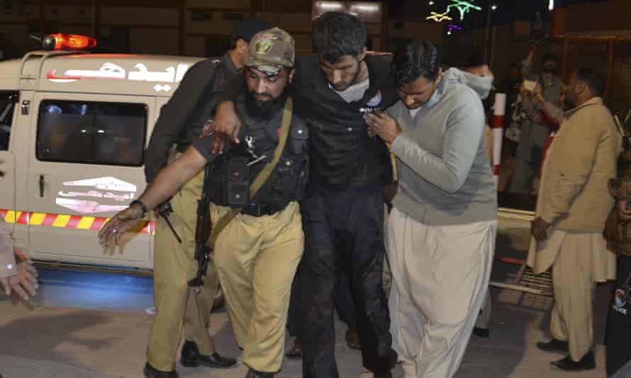 Rescuers help an injured person to a hospital in Quetta, Pakistan, after a hostel for police cadets was attacked by militants.
