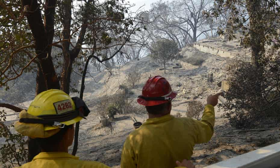Forest service personnel look over debris at a home burned by the fire at Palo Colorado Canyon in Big Sur, California.
