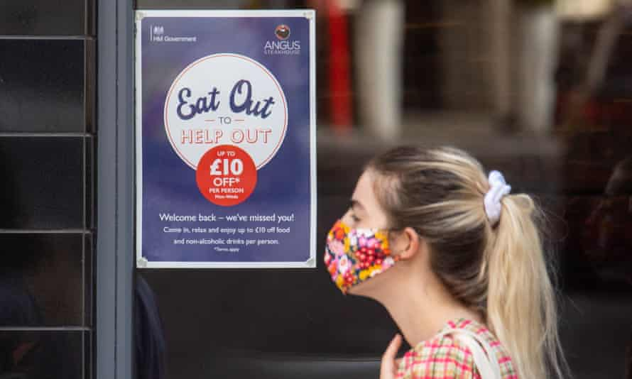 People pass a sign advertising the eat out to help out scheme, in Covent Garden, London