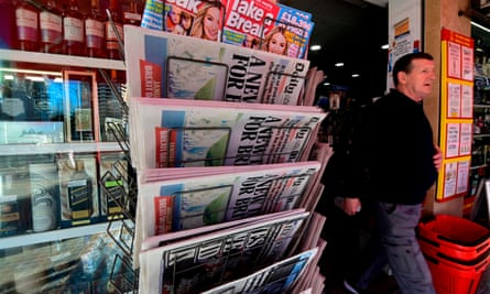 A man walks past a rack displaying British newspapers outside a supermarket in Benidorm in January