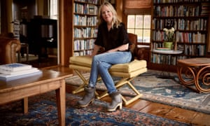Dani Shapiro, in jeans, a black top and ankle boots, at her home in Connecticut, in her study/library, surrounded by shelves of books and Persian rugs